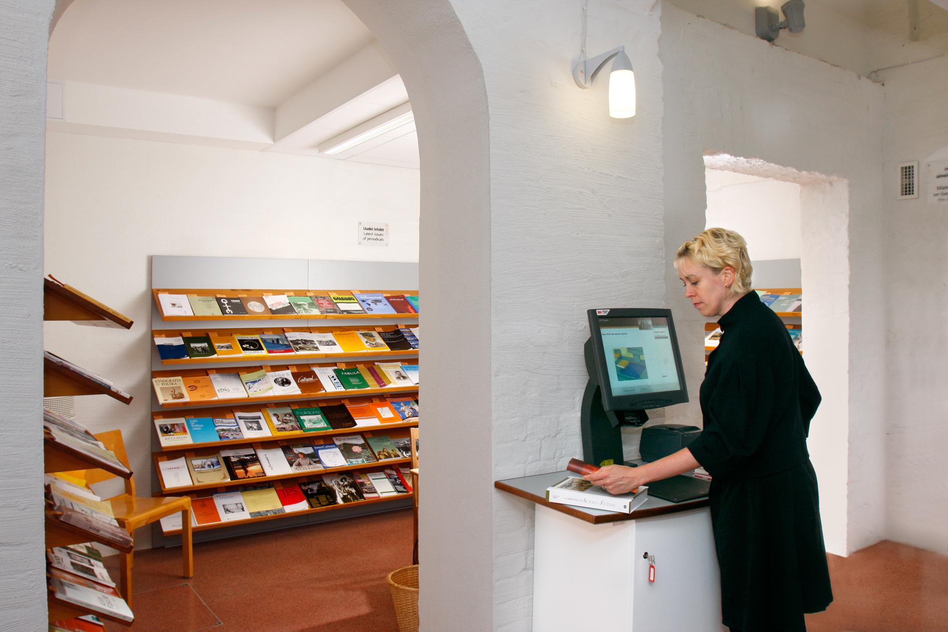 Itsepalvelua kirjaston lainausautomaatilla. SKS. Kuvaaja: Reijo Piispanen.